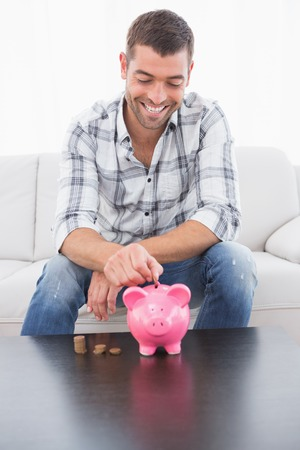 pennie: A man putting a pennie in a piggy bank on the sofa Stock Photo