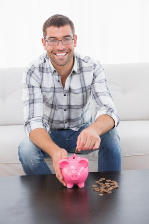 household money: A smiling man on the sofa putting coins in a piggy bank