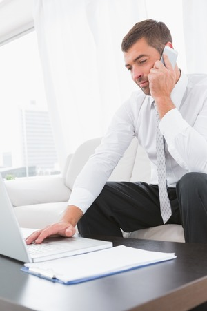 Smiling businessman on a phone with a laptop at home sitting on a sofa and a notebook photo