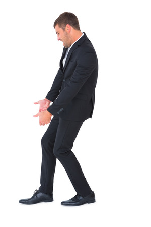contorted: Businessman contorted with hands downt on white background Stock Photo