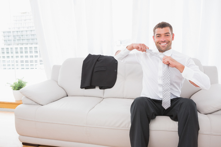 taking off: Businessman taking off his tie in his sofa Stock Photo