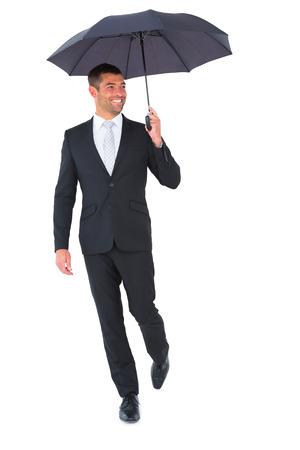 sheltering: Smiling businessman sheltering under black umbrella on white background Stock Photo