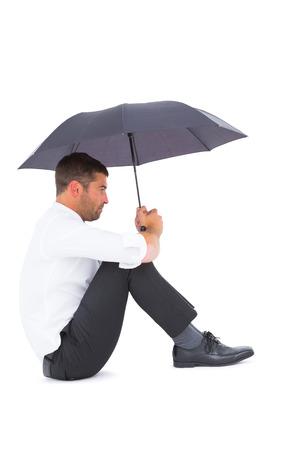 desolaci�n: Hombre de negocios sentado en el suelo con un paraguas negro sobre fondo blanco