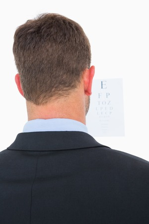 sense of sight: Focused man in suit on eye test letters on white background