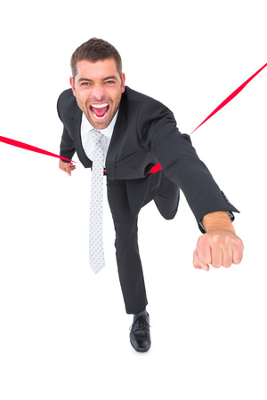 Businessman crossing the finish line on white background photo