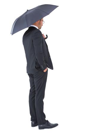 sheltering: Businessman sheltering under black umbrella on white background Stock Photo