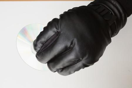 stolen identity: Hacker holding a cd-ro on white background