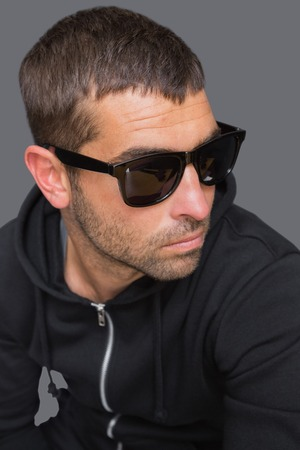 shadowy: Criminal with sunglasses looking at camera in a shadowy setting Stock Photo