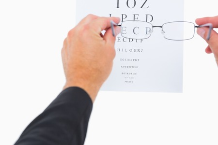 eye test: Glasses held up to read eye test on white background
