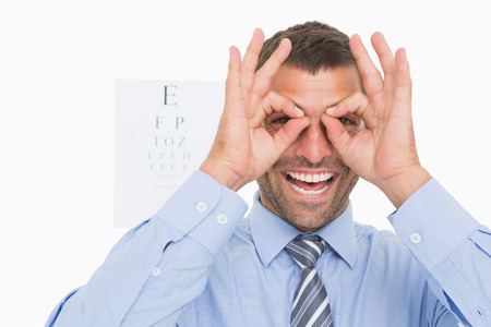 surrounds: Businessman surrounds his eyes with fingers on white background