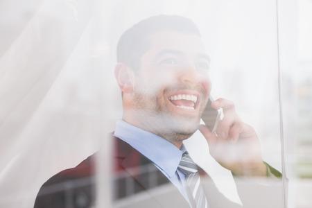 adentro y afuera: Sonriente hombre de negocios mirando por la ventana en el tel�fono en su oficina