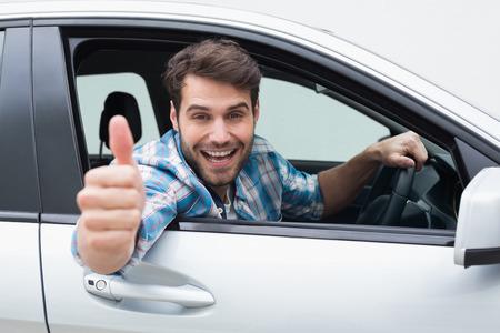happy young: Hombre joven sonriente y mostrando los pulgares para arriba en su coche Foto de archivo
