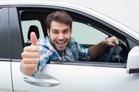 man: Young man smiling and showing thumbs up in his car