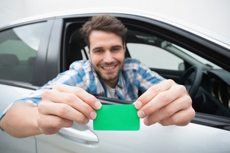 holding: Young man smiling and holding card in his car
