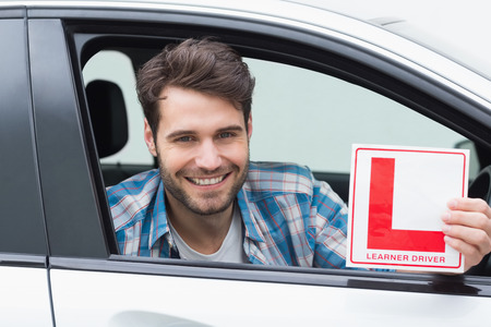 l plate: Learner driver smiling and holding l plate in his car