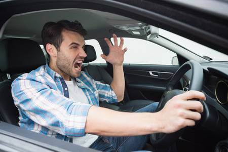 rage: Young man experiencing road rage in his car