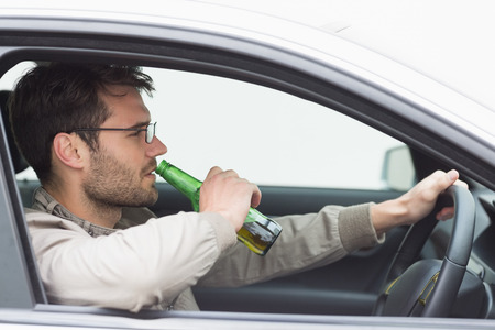 drinking and driving: Man drinking beer while driving in his car