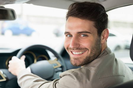 Young man smiling while driving in his car