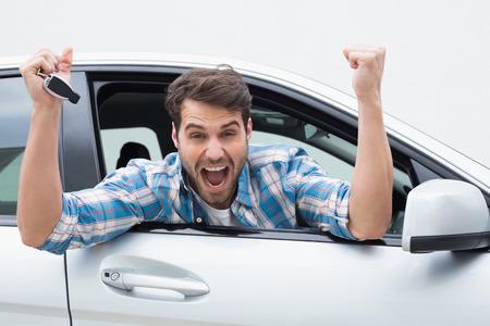Jonge man glimlachend en gejuich in zijn auto Stockfoto