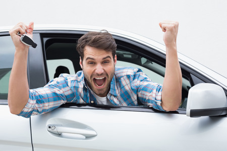 young cheering: Young man smiling and cheering in his car