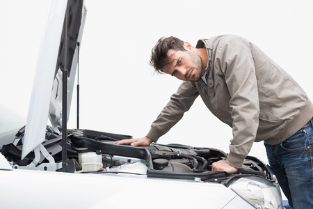 engine bonnet: Stressed man looking at engine of his car