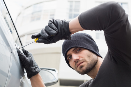 car theft: Thief breaking into car with screwdriver in broad daylight