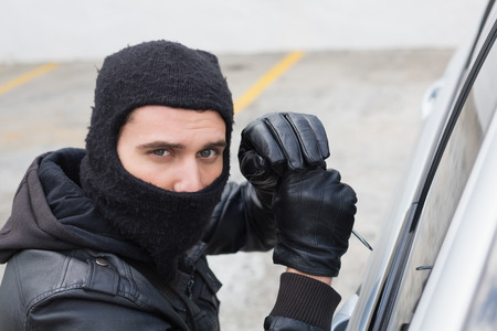 dishonesty: Thief breaking into a car in broad daylight Stock Photo