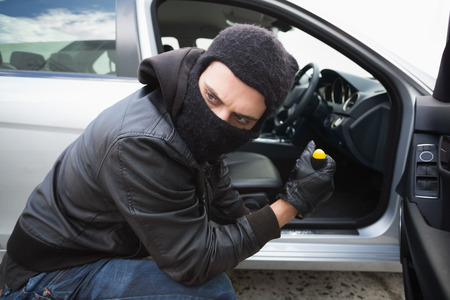 criminal activity: Thief breaking into car with screwdriver in broad daylight