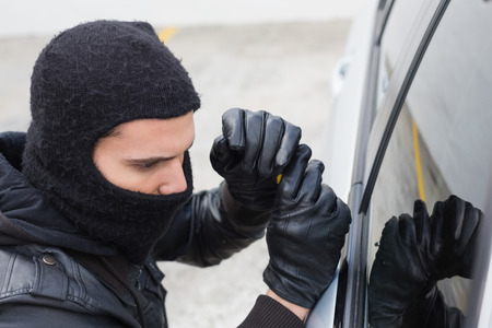 criminal activity: Thief breaking into a car in broad daylight Stock Photo