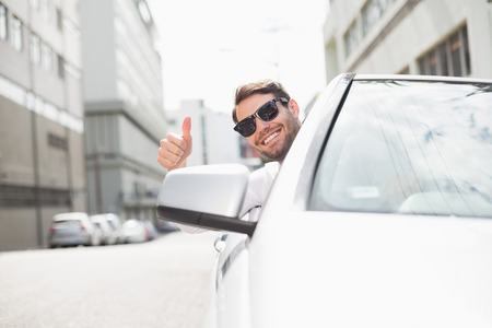 chofer: Hombre de negocios feliz en el asiento del conductor en su coche