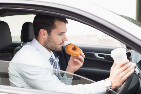 junk car: Young businessman having coffee and doughnut in his car Stock Photo
