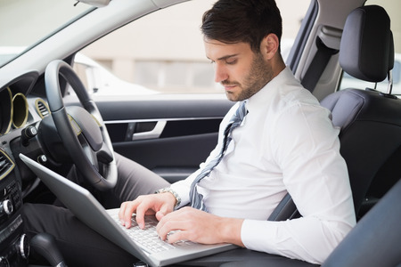drivers seat: Businessman working in the drivers seat in his car Stock Photo