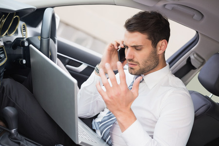 Businessman working in the drivers seat in his car photo