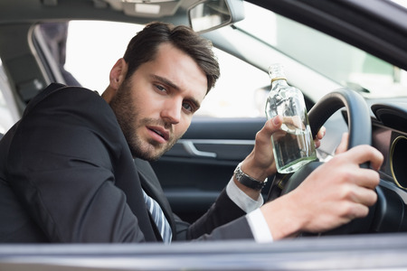 life threatening: Young businessman driving while drunk in his car