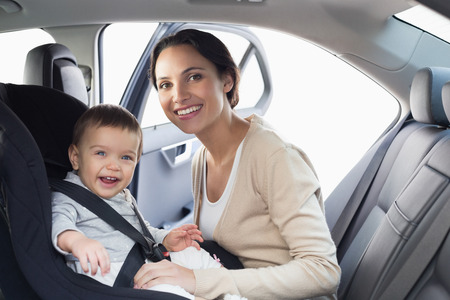 Mother securing her baby in the car seat in her car Standard-Bild
