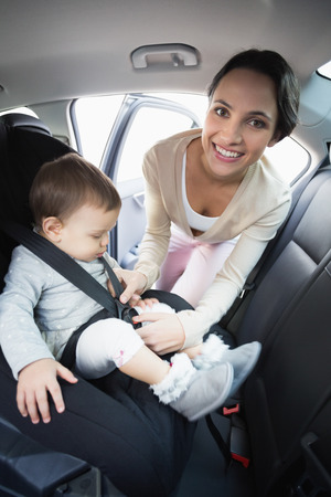 securing: Mother securing her baby in the car seat in her car Stock Photo