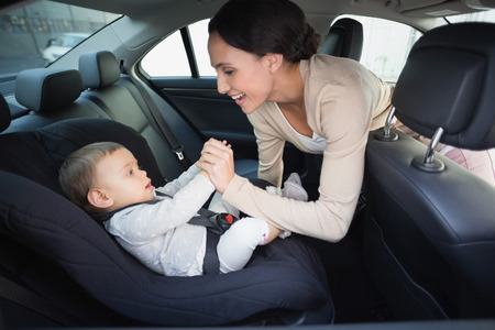 cars on road: Mother securing her baby in the car seat in the car Stock Photo