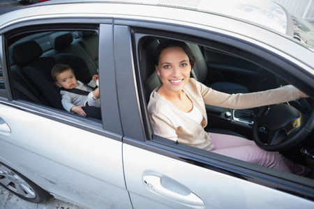 young child: Mother with her baby in the car seat in the car