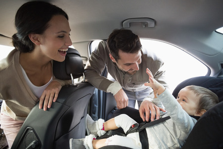 people street: Parents securing baby in the car seat in their car Stock Photo