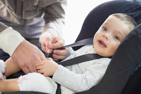 그의 차에서 자동차 좌석에 아기를 확보 부모