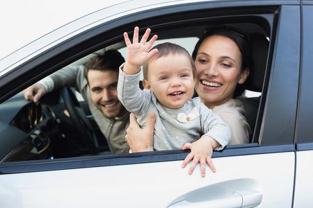 gente saludando: Padres y beb� en un coche en su coche