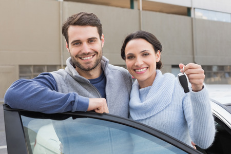 young caucasian: Young couple smiling holding new key outside their car