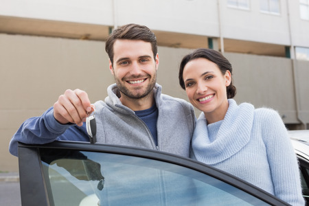 portrait couple: Young couple smiling holding new key outside their car