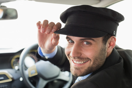 uniform attire: Handsome chauffeur smiling at camera in the car