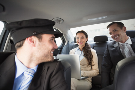 Handsome chauffeur smiling at clients in the car
