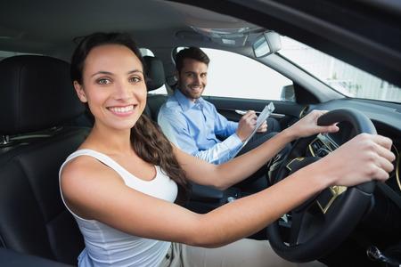 hombre conduciendo: Joven mujer recibiendo una lección de conducción en el coche
