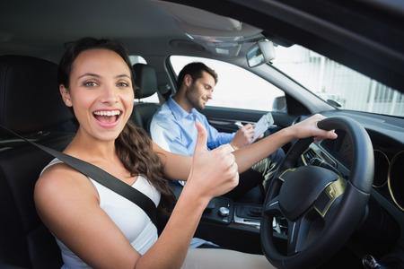 hombre conduciendo: Joven mujer recibiendo una lecci�n de conducci�n en el coche