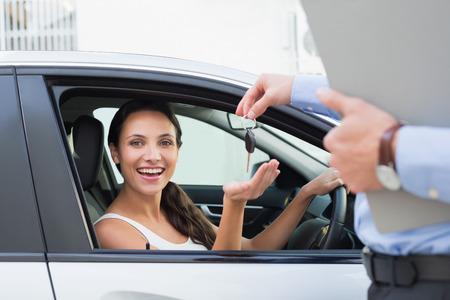 llaves: Mujer joven que consigue la llave en el coche Foto de archivo