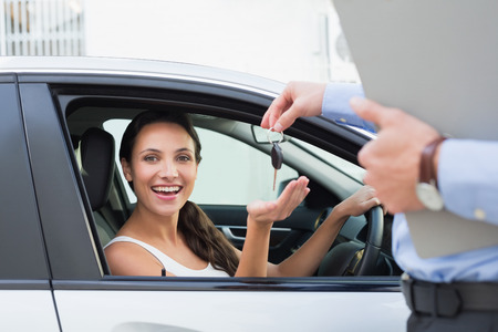 key: Young woman getting her key in the car Stock Photo