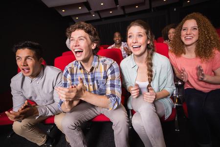 Amigos jovenes que miran una película en el cine Foto de archivo - 36447845